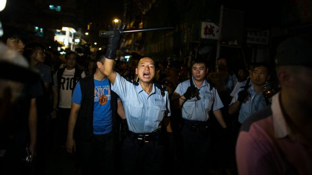 Identifiable: A policeman addresses the crowd during demonstrations in the Mong Kok area.