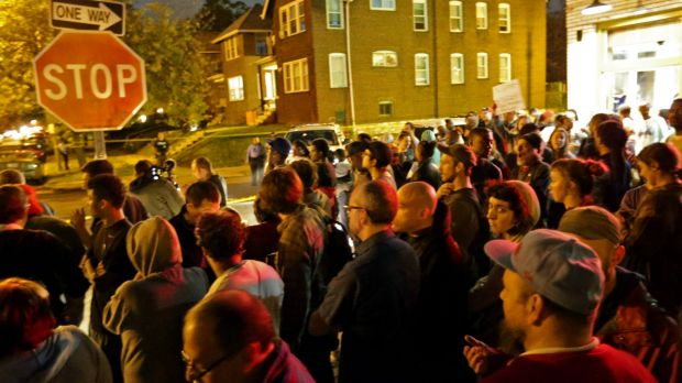 A crowd gathers near where a man was fatally shot by an off-duty St. Louis police officer