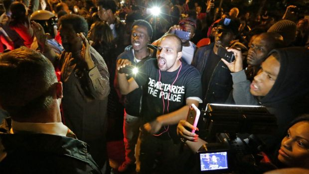 Crowds confront police near the scene of the shooting in south St. Louis.