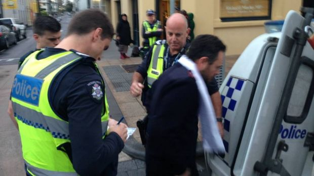 Salvation Army Captain Craig Farrell is taken away by police.