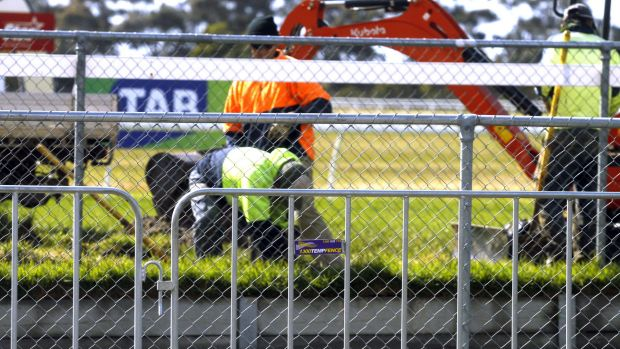 Track trouble ... workers fix the hole in the track at Werribee.