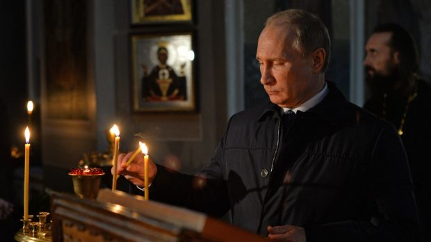 Russian President Vladimir Putin lights a candle while visiting the Lermontov museum in the village of Lermontovo near Penza.