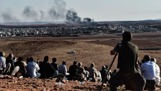 Natural grandstand: Kurdish people watch the battle for the Syrian town of Kobane from a hill in neighbouring Turkey.