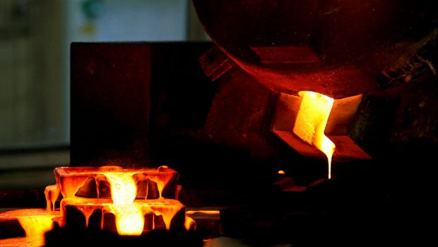 Mixed gold and silver are poured into ingot moulds at the Chatree gold mine's furnace in Thailand.