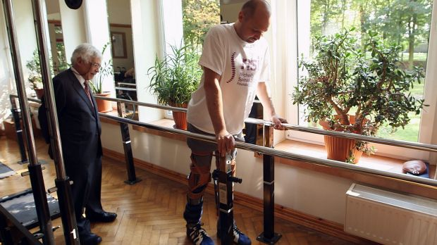 FIRST STEPS: Darek Fidyka walks with the aid of leg-braces and a walking frame at the Akron Neuro-Rehabilitation Center ...