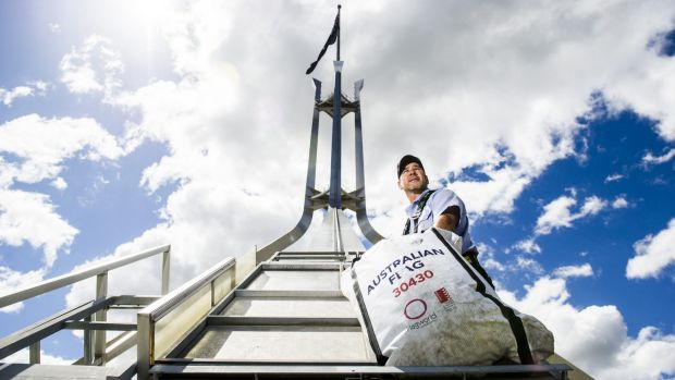 Flagged: Parliament House Maintenance Officer Jason Carew with a replacement flag in the three-man lift used to ascend ...