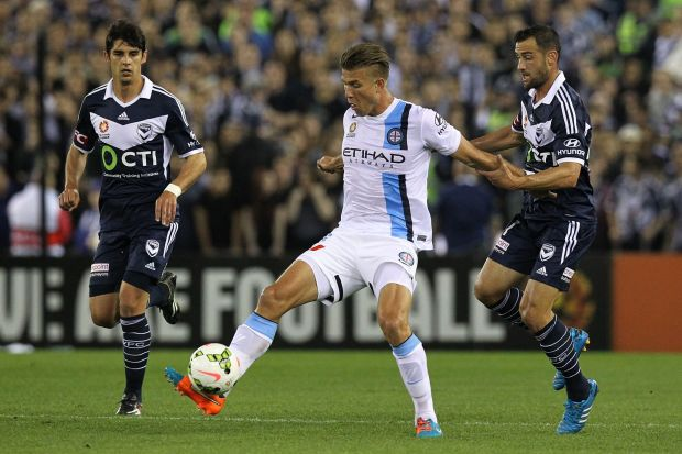 City's Erik Paartalu controls the ball as two Melbourne Victory defenders approach.