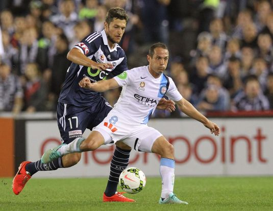 City's Massimo Murdocca looks to pass as Matthieu Delpierre of Melbourne Victory comes up behind him.