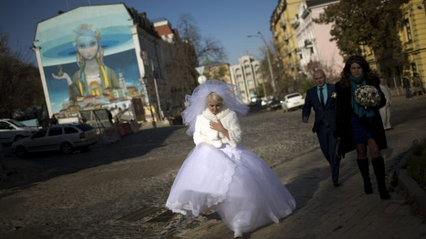 High hopes: A wedding party walks down the street in Kiev on Saturday.