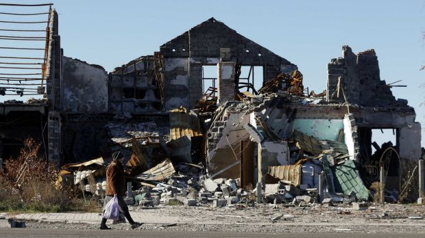 Ruined world: A woman walks near houses damaged by recent shelling in the outskirts of Slaviansk in rebel-held eastern ...