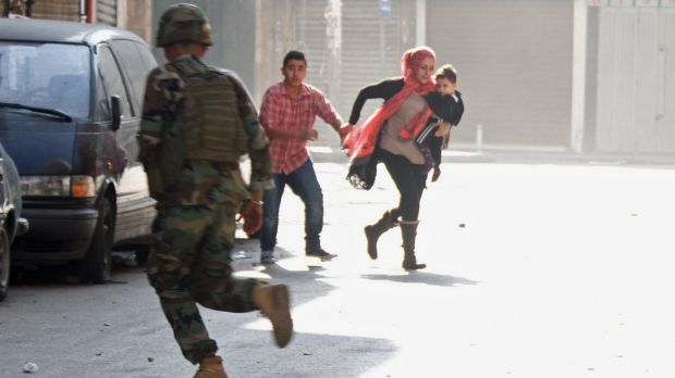 A Lebanese soldier runs past fleeing residents during the clashes in Tripoli, the country's second city, between ...
