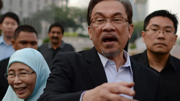 Malaysian Opposition leader Anwar Ibrahim (centre) gestures as he walk with his wife Wan Azizah (left) towards his ...