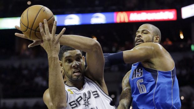 Winning start: San Antonio's Tim Duncan battles with Dallas centre Tyson Chandler.