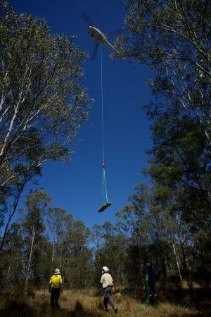 Logs are lifted by a helicopter into the heart of the Mulgoa Nature Reserve near Penrith.