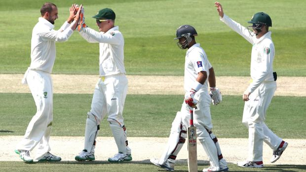 Nathan Lyon is congratulated after picking up the only wicket before lunch, trapping Ahmed Shehzad in front for 35.