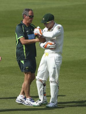 Painful: Brad Haddin gets treatment during the series against Pakistan in the UAE.