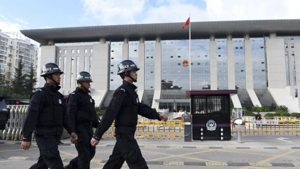 Chinese police patrol outside the court where the Kunming railway station bombers were tried. Photo: AP