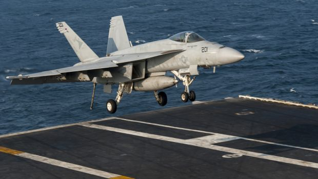 Air strikes continue ... A US fighter jet lands on the flight deck of the aircraft carrier USS Carl Vinson in the ...