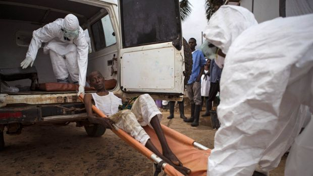 Health care worker assist a suspected Ebola sufferer in Sierra Leone. Organising workers in Africa has been a problem.