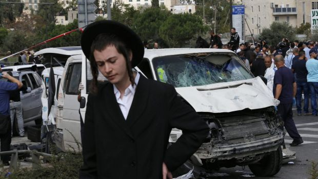 A Jewish man walks past the van used by a Palestinian motorist to ram into pedestrians in Jerusalem.