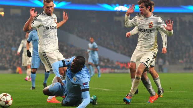 Down and nearly out: Yaya Toure is tackled by Vasily Berezutskiy (L) and Mario Fernandes.