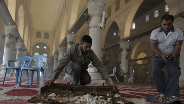 Palestinians clean up debris inside the al-Aqsa mosque on Wednesday following clashes between stone-throwing ...