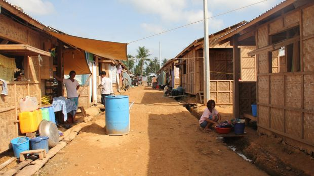 """Temporary thatched huts outside Tacloban are modest, but cooler than the notorious """"bunkhouses"""" in town."""