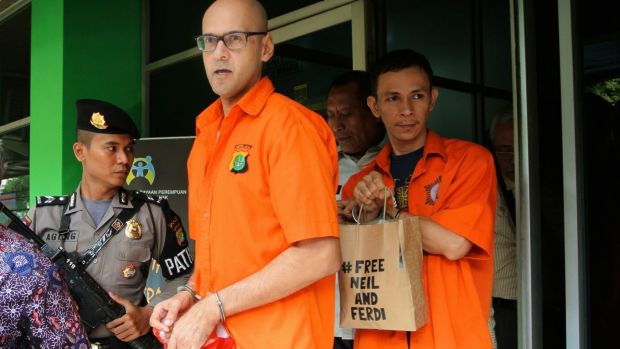 Neil Bantleman and Ferdinant Tjiong leaving the police station to be transferred to prison.