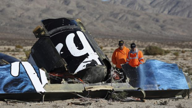 Out of the blue: Police look at wreckage of the Virgin Galactic SpaceShipTwo.