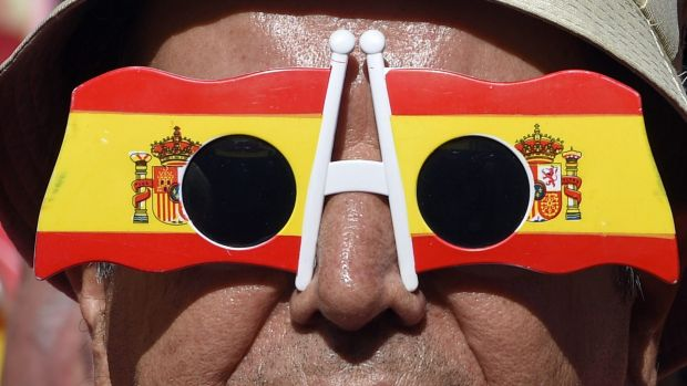 A Catalan signals his opposition to independence by wearing glasses bearing the Spanish flag.