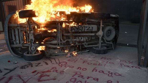 "A car burns next to graffiti reading ""If there is no justice for the people, shall be no peace for the government"" ..."