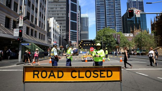 Construction workers organising the implementation of the light rail line closed roads in the central business district ...