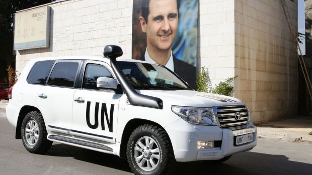 A poster of Syrian President Bashar al-Assad adorns a wall as the vehicle of United Nations special envoy for Syria ...