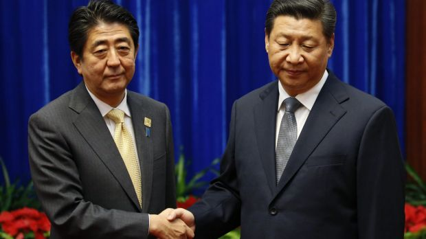 Japanese Prime Minister Shinzo Abe (left) and Chinese President Xi Jinping shake hands.