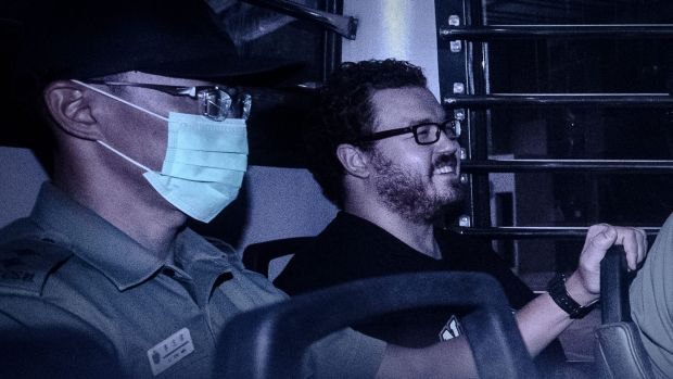 British banker Rurik Jutting, charged with the grisly murders of two women, smiles as he sits in a prison van leaving ...