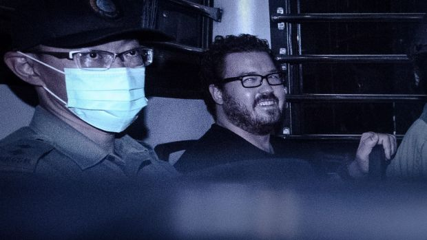 British banker Rurik Jutting, charged with the murders of two women, smiles as he sits in a prison van leaving the ...