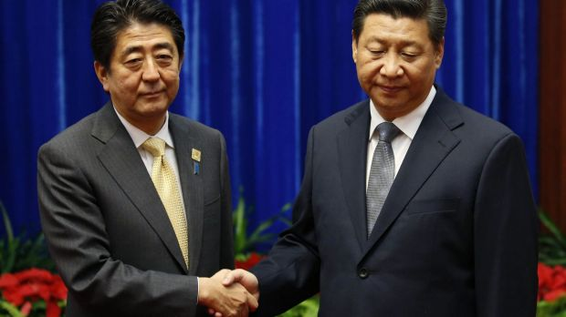 Uncomfortable: China's President Xi Jinping (right) shakes hands with Japan's Prime Minister Shinzo Abe.
