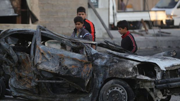 Fear factor: Iraqi children stand near a car destroyed by a bomb in the mostly Shiite district of Sadr City in northern ...