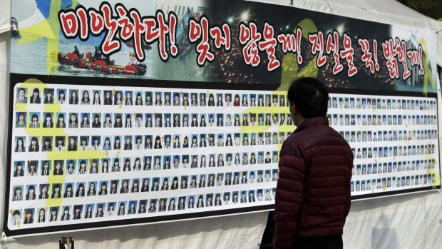 A man looks at portraits of the Sewol ferry disaster's victims on a poster in Seoul on Tuesday. The government has ...