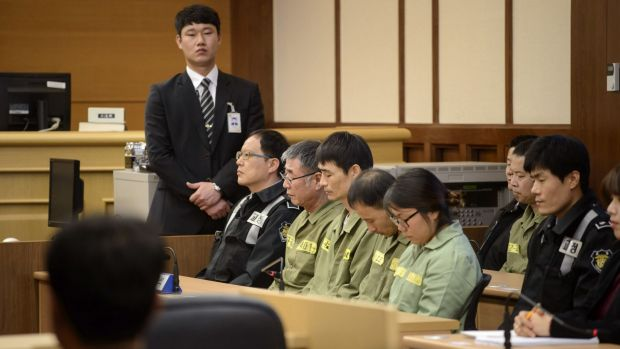 Sewol ferry captain Lee Joon-seok, in green prison garb with glasses, sits with crew members at the start of the reading ...