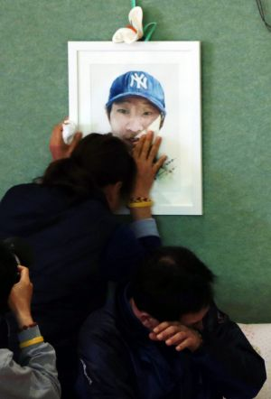 Relatives of a victim of the Sewol ferry disaster react to news that the search for bodies will end at a gym on Jindo ...
