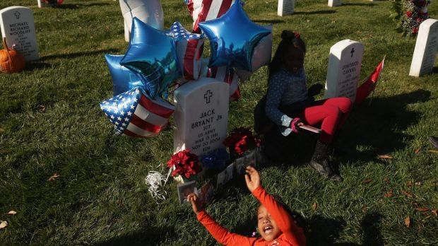 Families unite: Jayla Robinson plays at the grave of her uncle, Sergeant Jack Bryant, who died in Iraq in 2004.