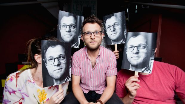 Carl Nilsson-Polias poses for a portrait with fellow staff members holding his 'famous' profile picture to their face.