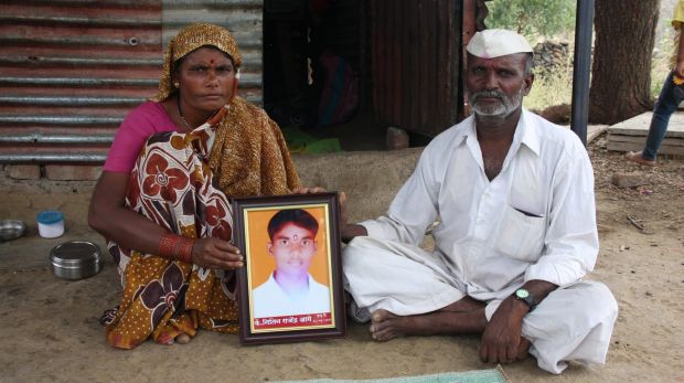 Bereft parents: Rekah and Raju Aage pose outside their home in Kharda with a portrait of their son, Nitin.