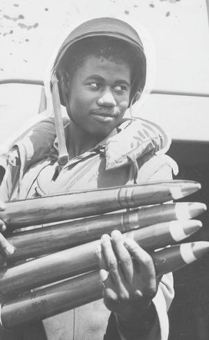 An African American soldier loads munitions during World War II.