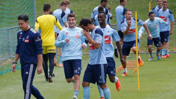 Terry Antonis, left, trains with Sydney FC while skipper Alex Brosque, centre, leaves the pitch after suffering an injury.