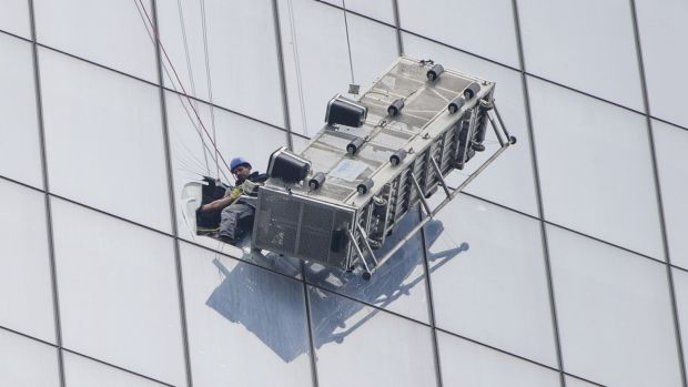 One of two window-washers is pulled to safety.