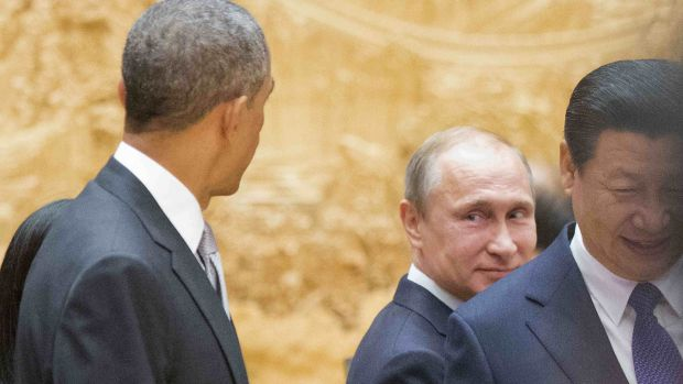 Russian President Vladimir Putin, centre, looks back at US President Barack Obama, left, as they arrive with Chinese ...