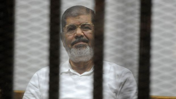 Deposed Egyptian president Mohamed Morsi sits behind bars during a trial in Cairo in early November.