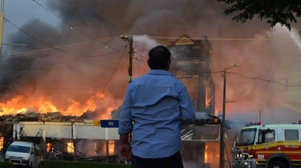 An onlooker watches on as the Royal Hotel, Roma burns.